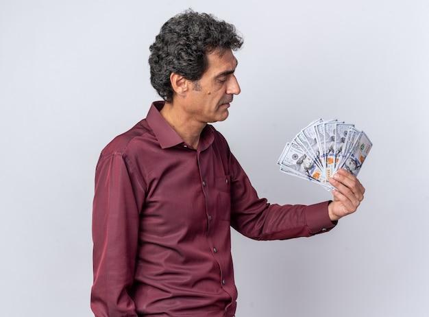 Homem sênior com camisa roxa segurando dinheiro e olhando para dinheiro com uma expressão séria