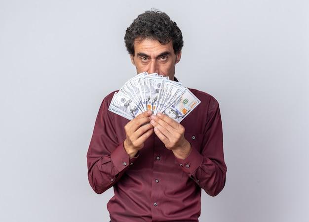 Homem sênior com camisa roxa segurando dinheiro na frente do rosto, parecendo confiante em pé sobre o branco
