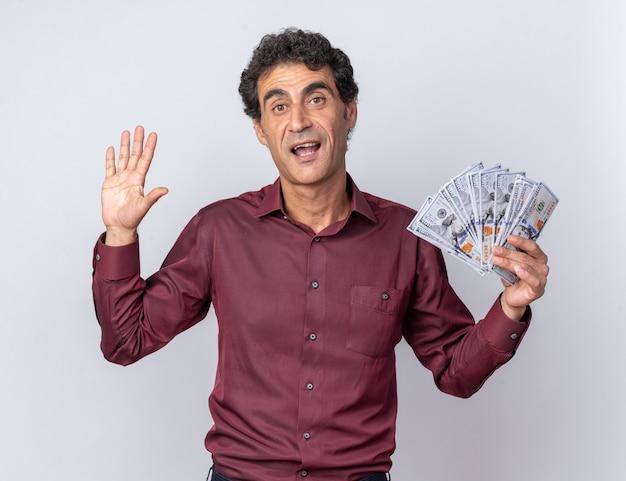 Homem sênior com camisa roxa segurando dinheiro olhando para a câmera feliz e confiante mostrando o número cinco