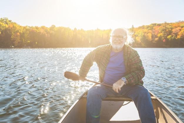 Homem sênior, com, canoa, remando, ligado, um, dia ensolarado