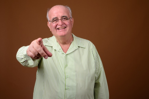 Homem sênior com excesso de peso usando óculos contra uma parede marrom