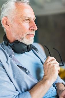 Homem sênior, com, headphone, ao redor, seu, pescoço, segurando, óculos