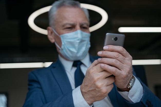 Homem sênior com máscara médica usando telefone celular, trabalhando online, foco nas mãos