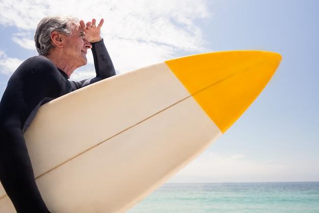Homem sênior com prancha de surf, protegendo os olhos na praia