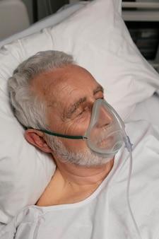 Homem sênior com respirador em uma cama de hospital