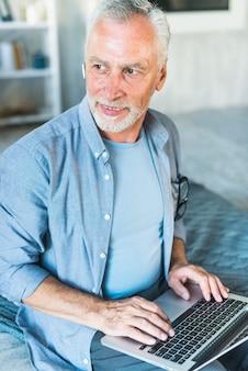Homem sênior, com, sem fios, bluetooth, usando computador portátil