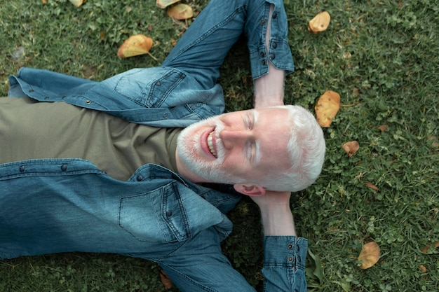 Homem sênior com tiro médio deitado na grama