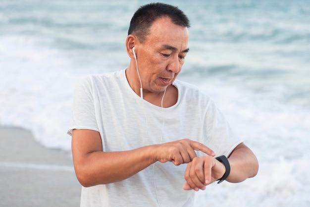 Homem sênior com tiro médio verificando o relógio