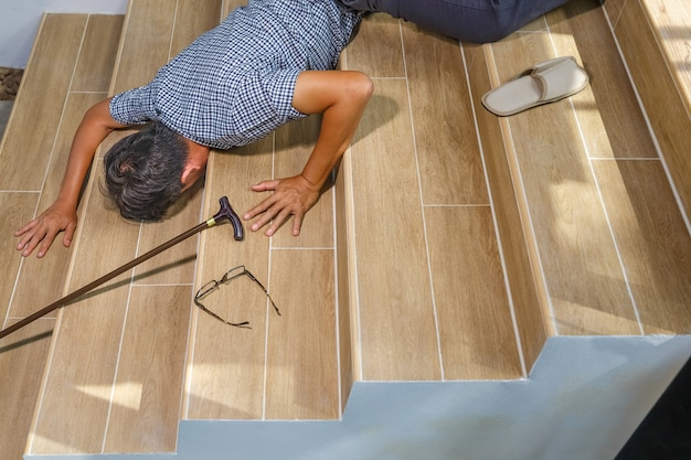 Homem sênior com um pedaço de pau caindo escada abaixo