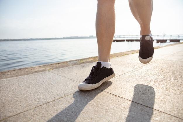 Homem sênior como corredor com braçadeira ou rastreador de fitness na margem do rio