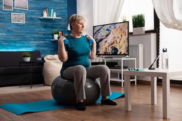 Homem sênior concentrado fazendo exercícios de resistência corporal, fazendo exercícios com os braços, usando halteres, sentado na bola suíça de fitness na sala de estar