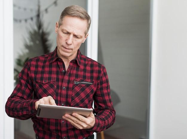 Homem sênior concentrado olhando no seu tablet