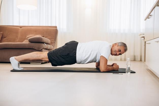 Homem sênior confiante em posição de prancha enquanto se exercita no chão no interior do loft de luz