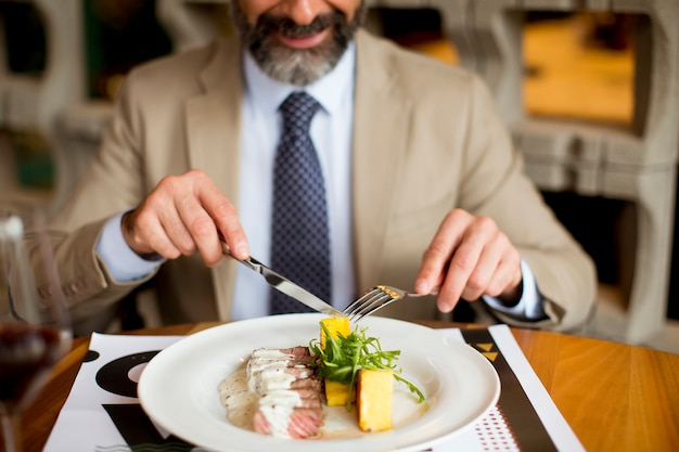 Homem sênior considerável que come o almoço no restaurante
