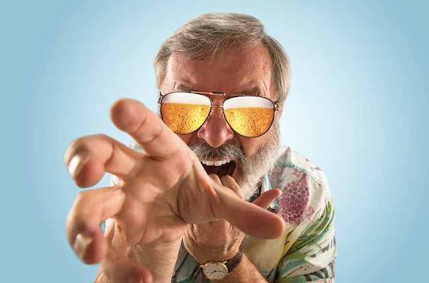 Homem sênior da oktoberfest com óculos de sol cheios de cerveja light, olhando para o mar ou oceano de álcool. expressão facial, espantado, louco feliz. a celebração, feriados, conceito de festival. tome uma cerveja.