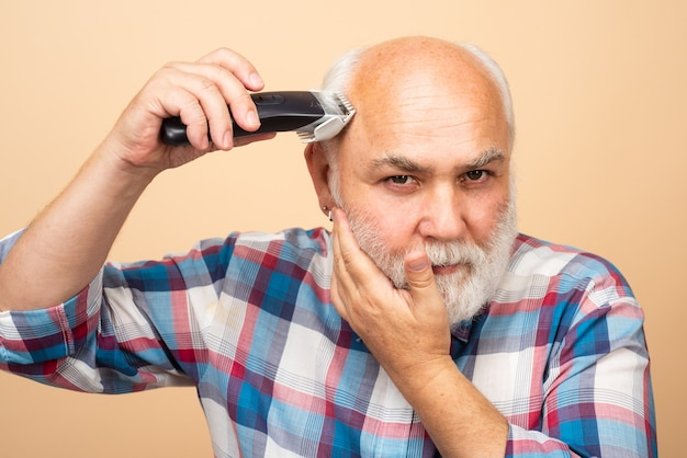 Homem sênior de cabeleireiro com máquina de cortar cabelo, corte de cabelo com barbeador elétrico. conceito de barbearia da barbearia.
