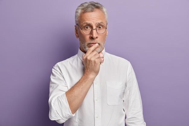 Homem sênior de camisa branca e gravata borboleta rosa