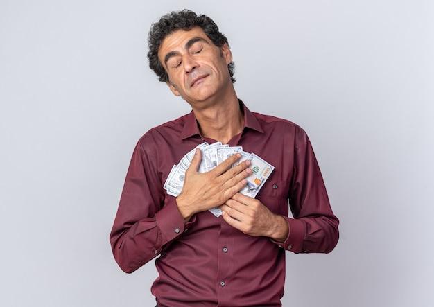 Homem sênior de camisa roxa segurando dinheiro com os olhos fechados e sentindo-se grato em pé sobre um fundo branco