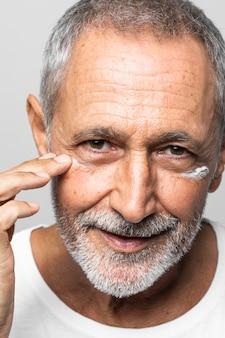 Homem sênior de close-up aplicando creme