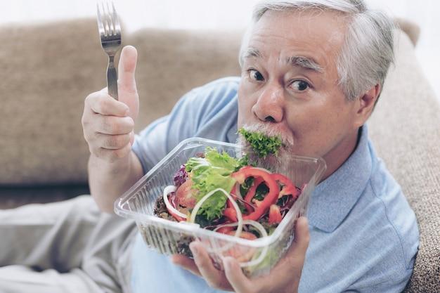 Homem sênior de estilo de vida se sentir feliz desfrutar de comer salada fresca de comida de dieta no sofá