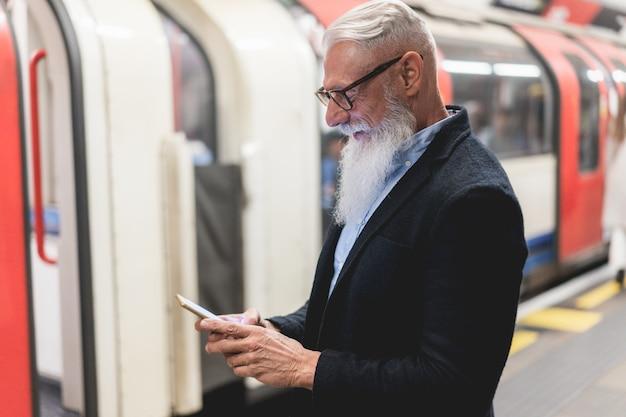 Homem sênior de negócios hipster usando telefone celular na estação de metrô - foco no rosto