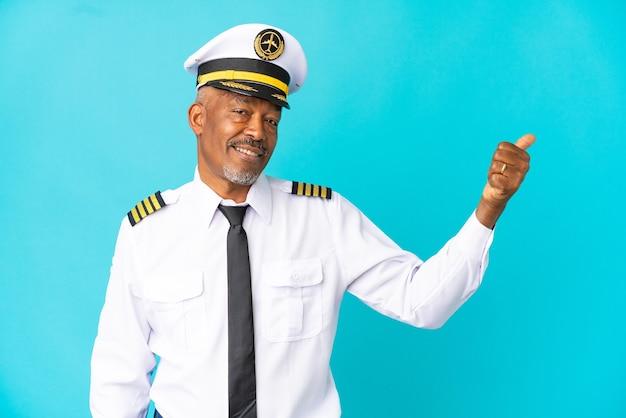 Homem sênior de piloto de avião isolado em fundo azul apontando para o lado para apresentar um produto