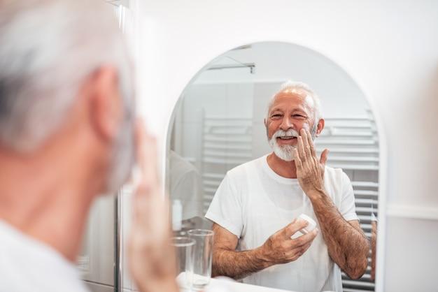 Homem sênior de sorriso que prepara sua barba no banheiro.