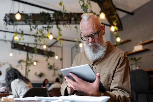 Homem sênior de tiro médio estudando com tablet