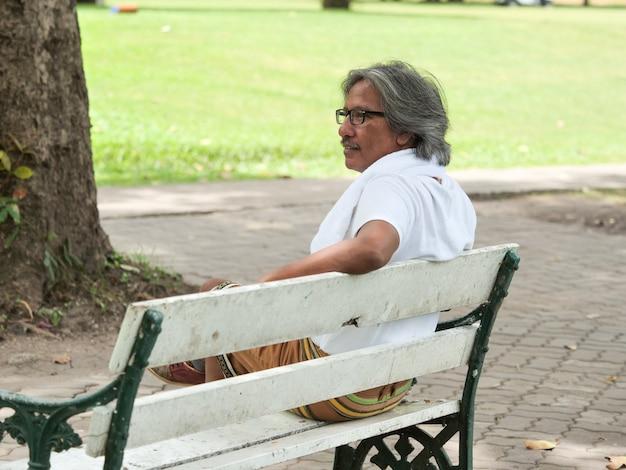 Homem sênior descansar no parque depois de andar de bicicleta
