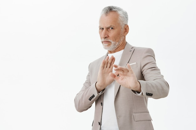 Homem sênior descontente e relutante levantando as mãos gesto de parada, rejeitando a oferta, fundo branco