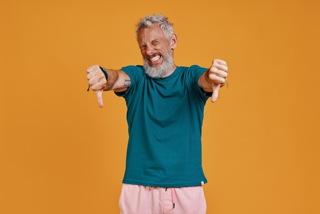 Homem sênior descontente olhando para a câmera e fazendo uma careta em pé contra um fundo laranja