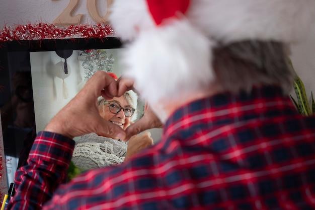 Homem sênior desfocado em videochamada, devido ao bloqueio por coronavírus, com a esposa sênior sorrindo fazendo um formato de coração com as mãos. em casa com computador e aparelhos tecnológicos