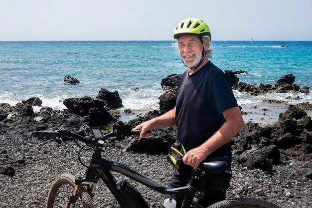 Homem sênior desportivo em pé com sua bicicleta e perto do mar. pessoas ativas pedalando para um estilo de vida saudável. ondas e rochas. conceito de aposentadoria feliz