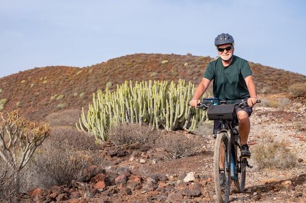 Homem sênior despreocupado em excursão ao ar livre em sua bicicleta elétrica, montanha ao fundo