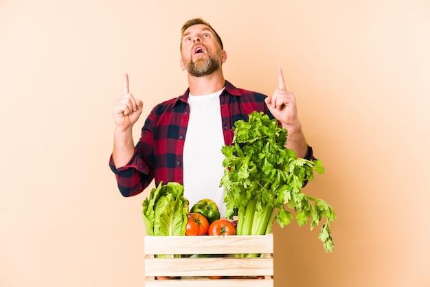 Homem sênior do agricultor na parede bege, apontando de cabeça com a boca aberta.