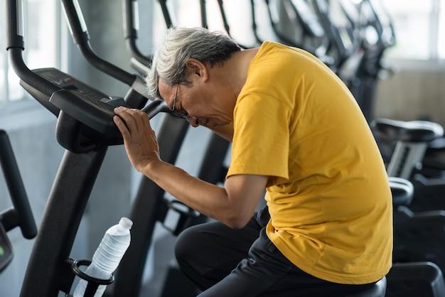 Homem sênior dos anos 60 de apagões exaustos após o exercício de bicicleta no ginásio de fitness. velho com cabelos grisalhos de cabeça baixa devido a choque, ataque cardíaco, tontura. acidente idoso de treinamento esportivo. saudável e seguro
