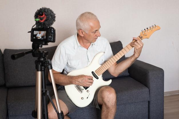 Homem sênior durante a quarentena, percebendo a importância de ficar em casa durante o surto do vírus. tocando violão. conceito de bloqueio de coronavírus, auto-isolamento, saúde, segurança