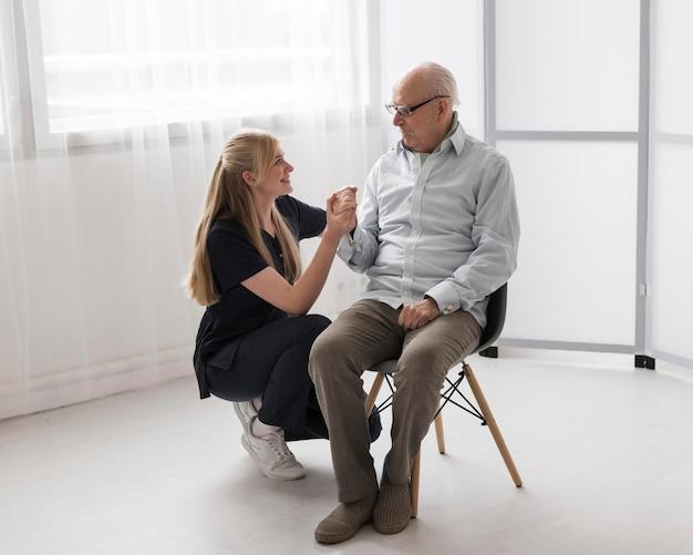 Homem sênior e enfermeira em uma casa de saúde juntos
