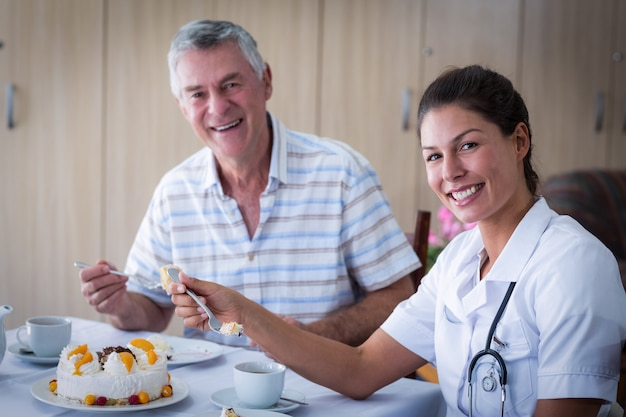Homem sênior e médica falando enquanto come bolo na sala de estar