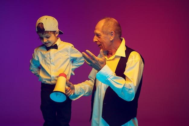 Homem sênior e menino em um fundo gradiente, copyspace