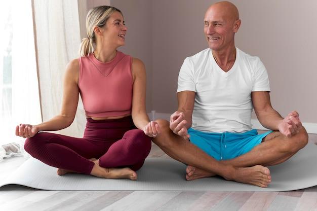 Homem sênior e mulher sentados em posição de lótus