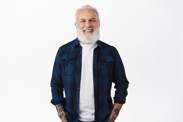 Homem sênior elegante com barba comprida, tatuagens e cabelos grisalhos, sorrindo e parecendo feliz na frente, conceito de propaganda, em pé contra uma parede branca