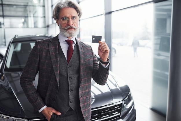 Homem sênior elegante com cabelos grisalhos e barba fica contra o carro preto moderno com cartão de crédito na mão.