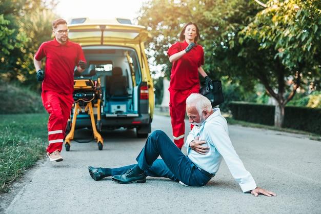 Homem sênior elegante com sintomas de ataque cardíaco, sentado na estrada, trabalhadores de serviços médicos de emergência tentando ajudá-lo.