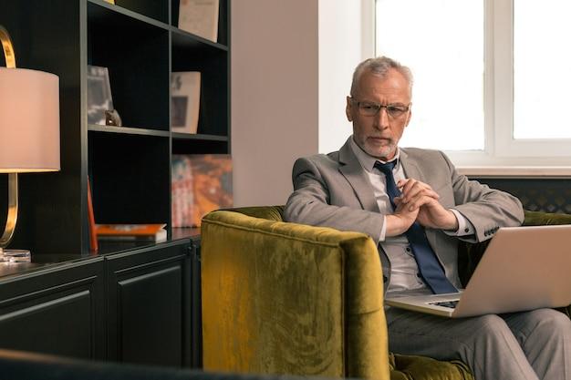 Homem sênior elegante e pensativo, sentado na poltrona em seu escritório, olhando para longe
