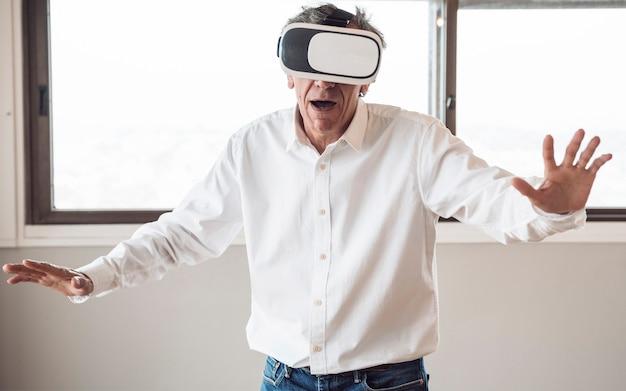 Homem sênior, em, camisa branca, usando, um, virtual, realidade, headset, em, a, sala