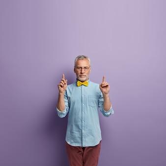 Homem sênior em camisa jeans e gravata borboleta amarela