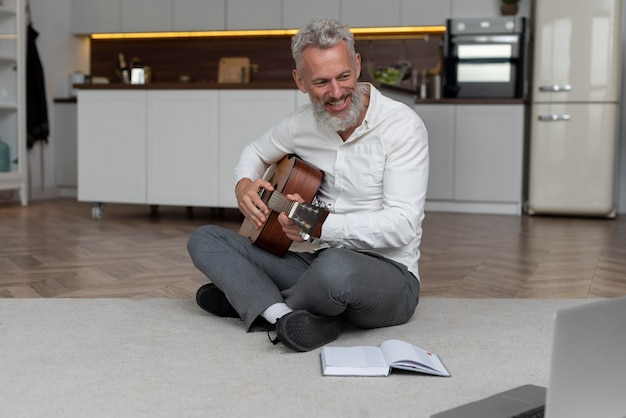 Homem sênior em casa no chão, tendo aulas de violão