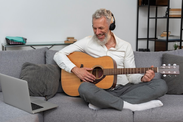 Homem sênior em casa no sofá usando laptop para estudar aulas de violão