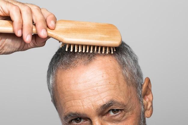 Homem sênior em close-up escovando o cabelo